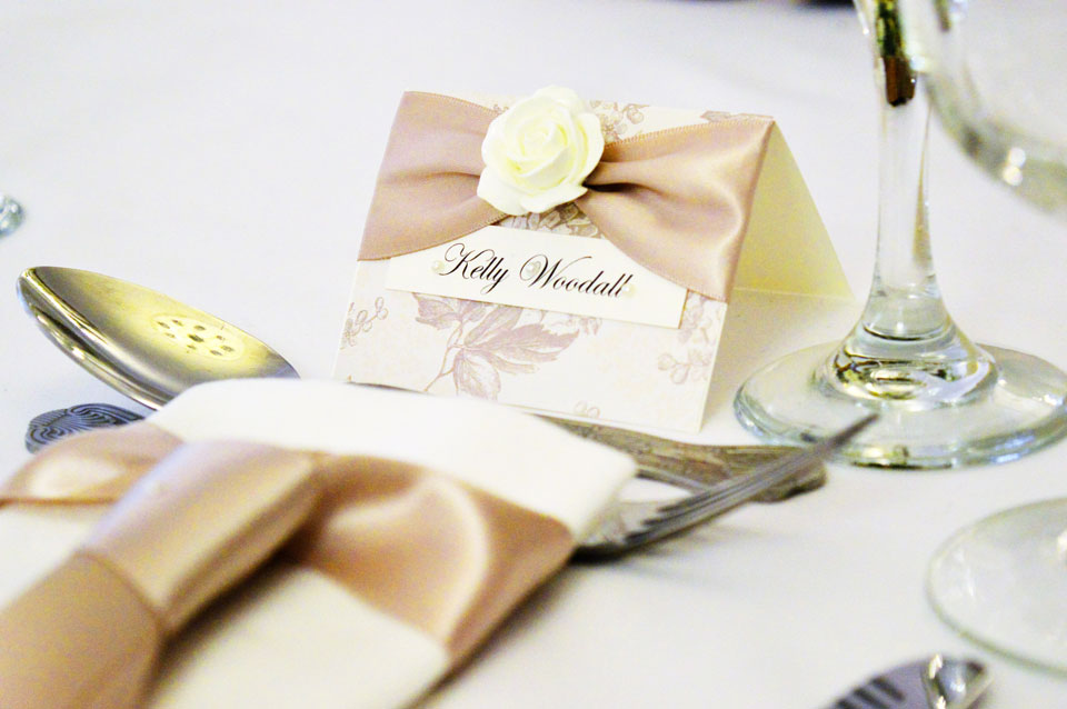 Decorative floral card with cappuccino satin bow and ivory rose name place card