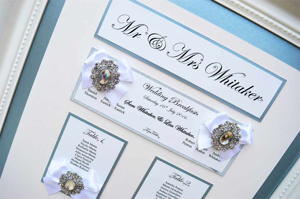 Framed wedding table plan in satin blue with a white bow by Charlotte Designs