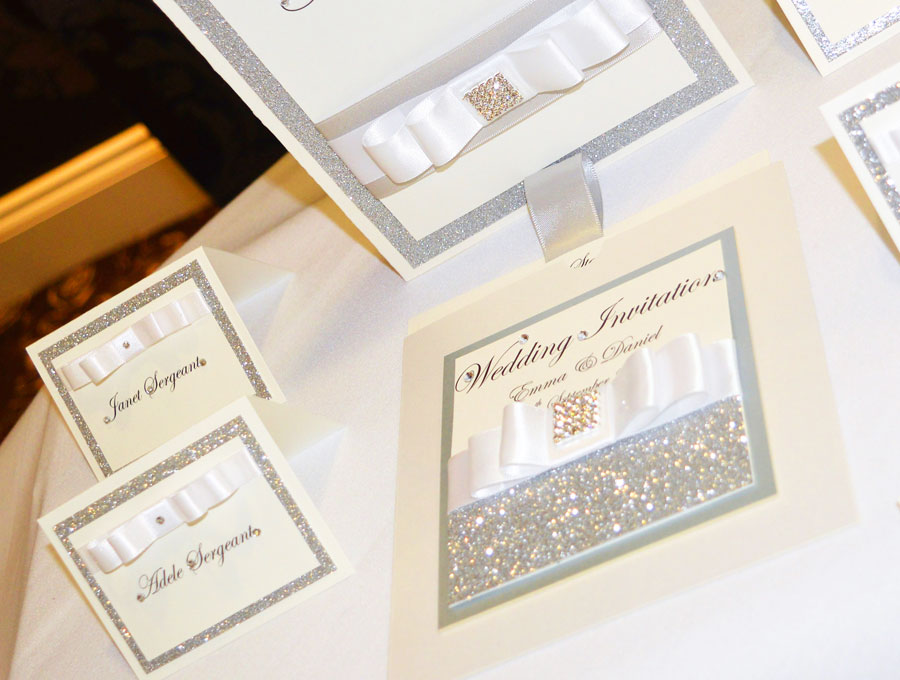 Silver sparkle and white name place cards and matching wedding invitation