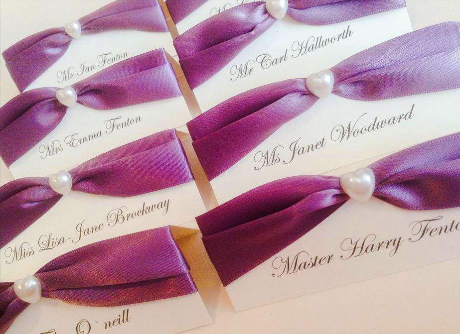 Name place cards with purple satin ribbon and pearl heart adornment