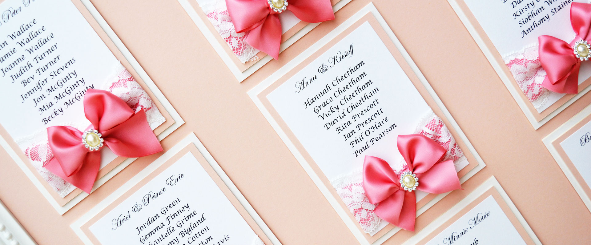 Beautiful table plan with pink satin and white lace bows, blush pink background and a pearl embellishment