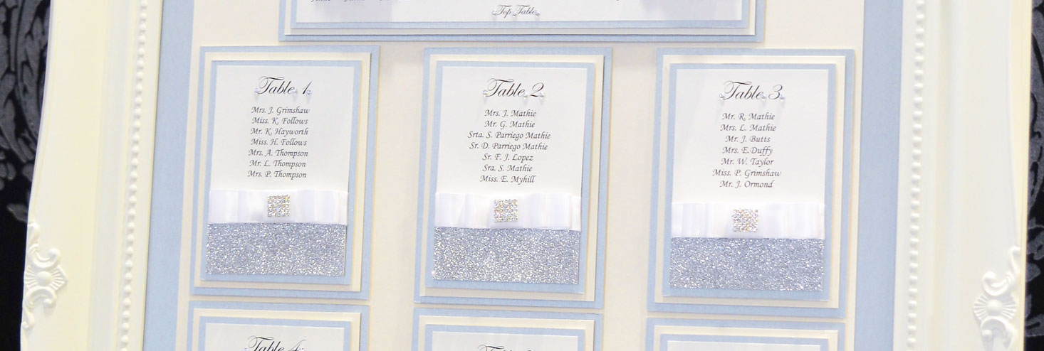 Close up of framed table plan with square diamante brooch, silver sparkle paper and white folded bows