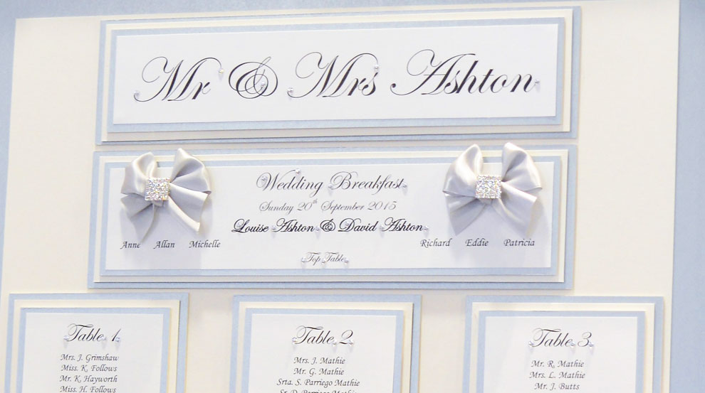 Silver framed table plan with square diamante brooch, silver sparkle paper and white folded bows
