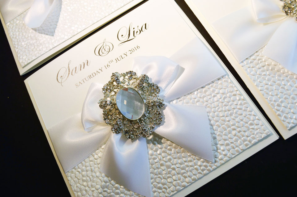 Wedding invitation with pearl effect embossed card with white satin bow and vintage embellishment