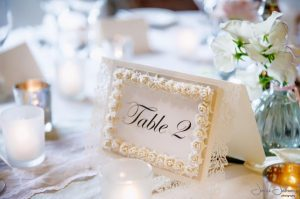 Elegant wedding table number with embellished roses on white card