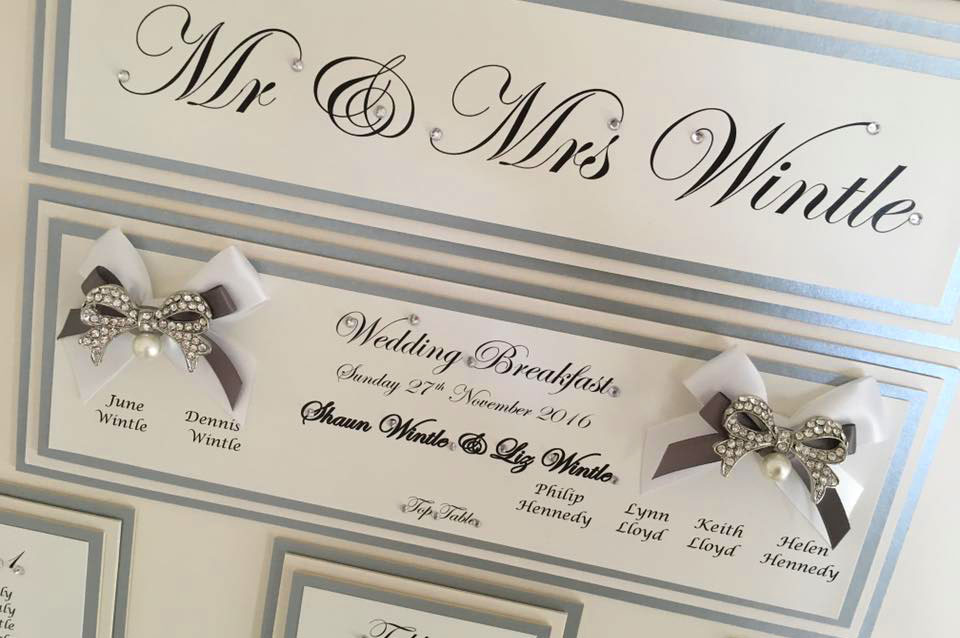 Wedding table plan with silver and white satin bow design