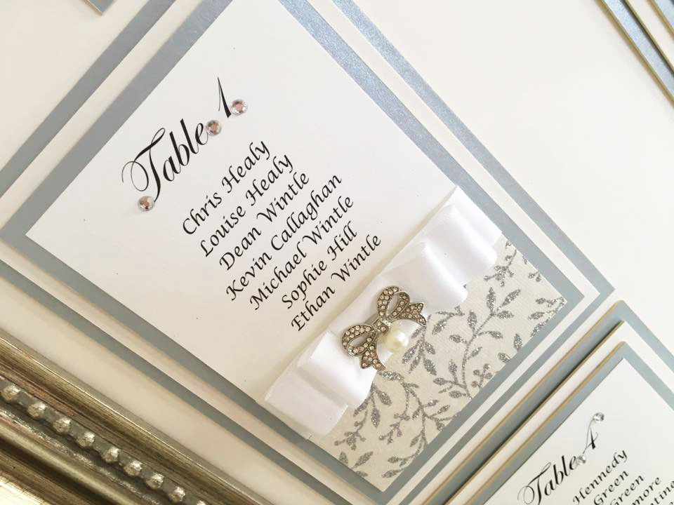 Wedding table plan grey and white satin bow with a sparkly silver leaf design by Charlotte Designs