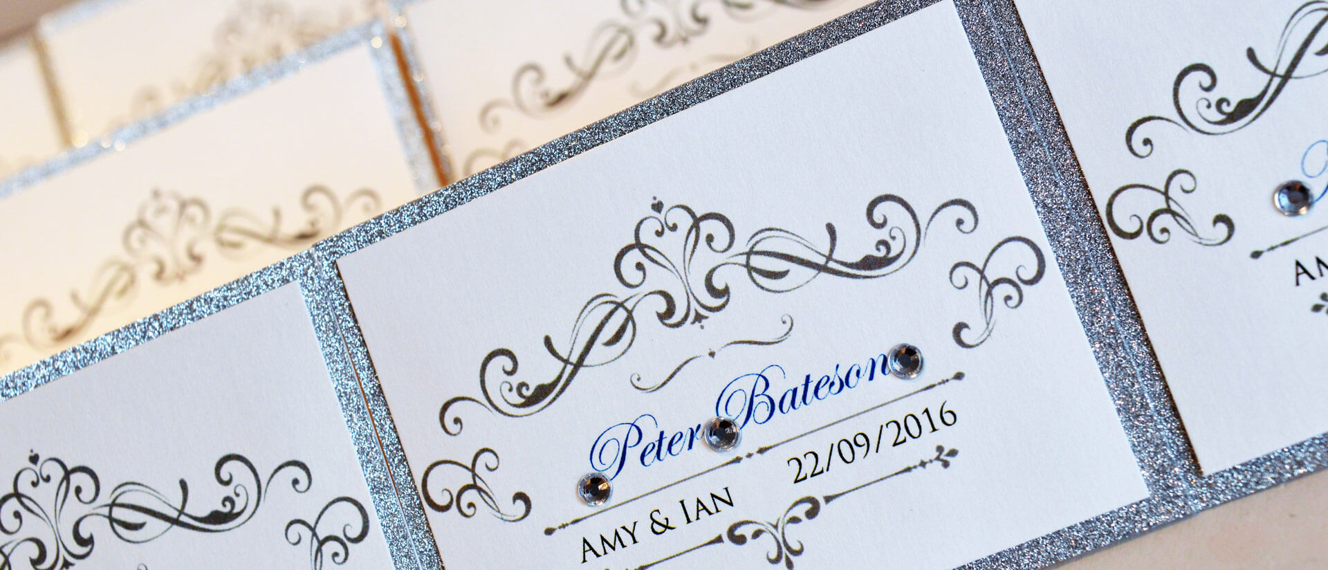 Stunning handmade silver and white sparkly name place cards by Charlotte Designs