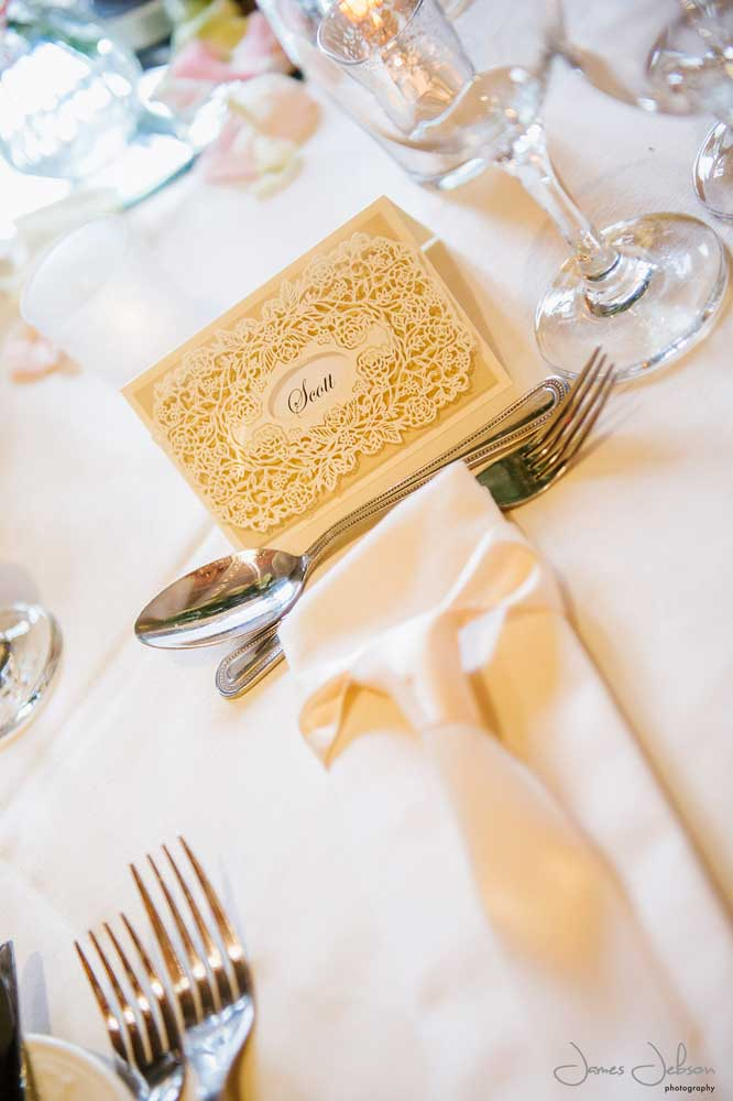 Intricate ivory laser cut name place card with matching satin tie napkin dressing